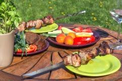 Blandat läckert grillat kött med grönsaken på picknicktabellen för familjbbq-parti Royaltyfria Bilder