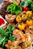 Blandat läckert grillat kött och grönsaker med ny sallad och bbq-sås på skärbräda på träbakgrundsslut upp bifokal arkivfoto