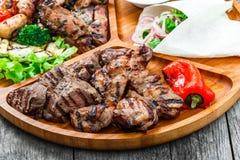 Blandat läckert grillat kött och grönsaker med ny sallad och bbq-sås på skärbräda på träbakgrundsslut upp Royaltyfria Bilder