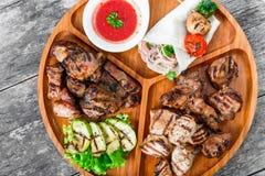 Blandat läckert grillat kött och grönsaker med ny sallad och bbq-sås på skärbräda på träbakgrundsslut upp Arkivbilder