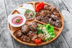 Blandat läckert grillat kött och grönsaker med ny sallad och bbq-sås på skärbräda på träbakgrundsslut upp Royaltyfri Fotografi