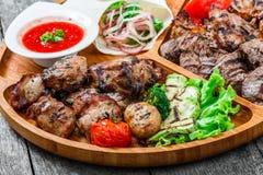 Blandat läckert grillat kött och grönsaker med ny sallad och bbq-sås på skärbräda på träbakgrundsslut upp Royaltyfri Bild