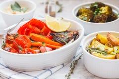 Blandning av bakade grönsaker i den vita keramiska formen med hummus Arkivfoto