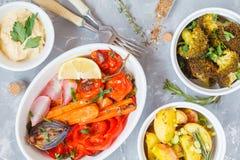 Blandning av bakade grönsaker i den vita keramiska formen med hummus, bästa v Fotografering för Bildbyråer