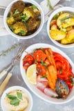 Blandning av bakade grönsaker i den vita keramiska formen med hummus, bästa v Royaltyfria Bilder