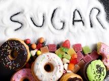 Blandning av den sötsakkakor, donuts och godisen med spridd och skriftlig text för socker i sjuklig näring Arkivbild