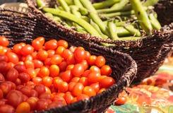 Blandning av färgrika körsbärsröda tomater och radbönor i korgar Arkivfoto