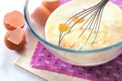 Blandning av kräm, vita choklad för melt och ägg arkivbilder
