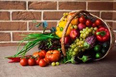 Blandning av nya grönsaker, frukter och grönsallat i vide- korg Fotografering för Bildbyråer
