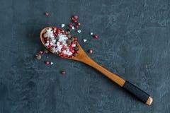 Blandning av peppar och en viktig vit var hav som är salt i en träsked mörkt bakgrundskopieringsutrymme royaltyfria foton