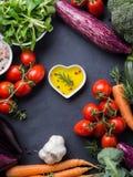 Blandning av rå grönsaker med salt, kryddor på mörker Royaltyfria Foton