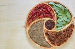Blandning av varma kryddor på träplattan: stjärnaanis, lagerbladar, paprika, torkade kryddnejlikor och nära övre för spiskummin K Arkivfoton