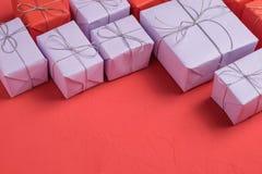 Blandningen av gåvor som slås in i lila och rött papper royaltyfria foton