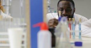 Blandningloppgrupp av forskare som tillsammans arbetar i modernt laboratorium som under analyserar kemikalieer i provrör, flaska arkivfilmer