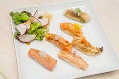 Blandningsushi för den selektiva fokusen grillade på den vita plattan; japansk mat Arkivbilder