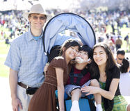 Blandras- familj i folkmassa med det rörelsehindrade barnet i rullstol arkivbild