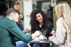 Blandras- grupp av fyra vänner som har ett kaffe tillsammans royaltyfri bild