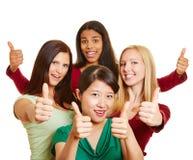 Blandras- grupp av kvinnor som rymmer upp tummar Arkivfoto