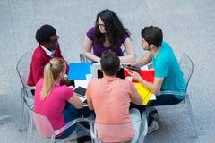 Blandras- grupp av unga studenter som tillsammans studerar Högt vinkelskott av ungdomarsom sitter på tabellen Arkivfoton