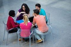 Blandras- grupp av unga studenter som tillsammans studerar Högt vinkelskott av ungdomarsom sitter på tabellen Royaltyfri Foto