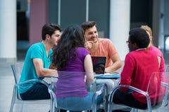 Blandras- grupp av unga studenter som tillsammans studerar Högt vinkelskott av ungdomarsom sitter på tabellen Arkivbild
