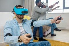 Blandras- grupp av vänner som har gyckel som försöker på skyddsglasögon för virtuell verklighet 3D arkivfoto