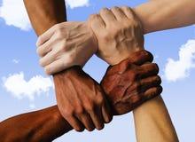 Blandras- grupp med den Caucasian svarta afrikanska amerikanen och asiatiska händer som rymmer sig handled i toleransenhetförälsk arkivfoto