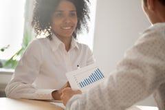 Blandras- kollegor som analyserar företagsstatistik under resumé royaltyfri foto