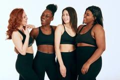 Blandras- kvinnlig med den olika format- och etnicitetställningen tillsammans och leende fotografering för bildbyråer