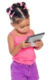 Blandras- liten flicka som använder en minnestavladator Royaltyfri Fotografi