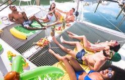 Blandras- lyckliga vänner som har att koppla av gyckel på, seglar fartygpartiet - kamratskapbegrepp med mång- ras- folk på katama arkivbilder