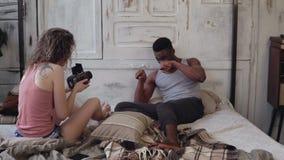 Blandras- photoshoot Fotografkvinna som tar fotoet av den roliga mannen i pyjamas på flyttning-film kamera på sängen lager videofilmer
