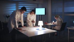 Blandras- teknikerer för elektronikutvecklingsteknikerer som diskuterar intrig för kontrollelektronik i laboratorium lager videofilmer