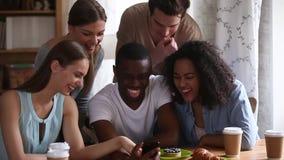 Blandras- unga vänner som håller ögonen på den roliga mobila videoen på smartphonen stock video