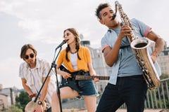 Blandras- ungdomarmed gitarrdjembe och att utföra för saxofon royaltyfri bild