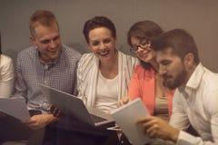 Blandras- ungt id?rikt folk i modernt kontor Gruppen av ungt aff?rsfolk arbetar samman med b?rbara datorn arkivbilder