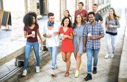 Blandras- vängrupp som går i centrum - lyckliga grabbar och flickor som har gyckel runt om gamla stadgator - universitetsstudente arkivfoto