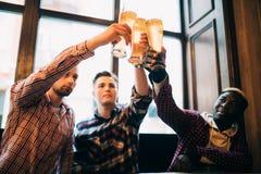 Blandras- vänmanjubel med öl i exponeringsglas i bar Rosta ölbaren royaltyfri fotografi