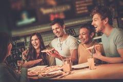 Blandras- vänner som har gyckel som äter i pizzeria royaltyfri fotografi