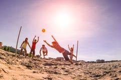 Blandras- vänner som spelar fotboll på stranden - begrepp av mång- c royaltyfria foton