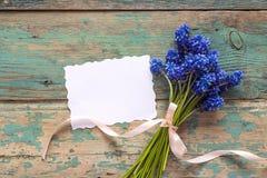Blankblommar det pappers- kortet med buketten av den blåa muscarien på gammalt PA Royaltyfri Foto