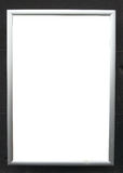 Blank advertisement board on black wall Stock Photography
