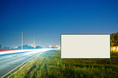 Blank advertising billboard by the road. Empty advertising billboard by the busy road at night with traffic light trails stock photo