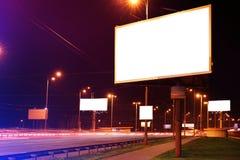 Blank advertising board on city street. At night Stock Photos