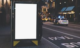 Blank advertising light box on bus stop, mockup of empty ad billboard on night bus station, template banner on background city. Street for poster or sign in royalty free stock photo