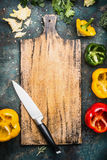 Blank aged wooden cutting board with kitchen knife and Bell colorful paprika peppers Royalty Free Stock Photos