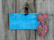 Blank antique blue sign with red hearts and iron keys hanging on shabby wooden background Royalty Free Stock Images