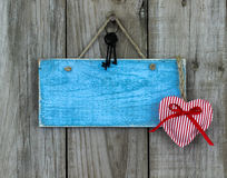 Blank antique blue sign with red and white striped heart and iron keys hanging on rustic wooden background Royalty Free Stock Image