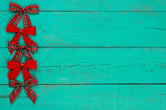 Blank antique green distressed wooden background with red plaid and velvet Christmas bow border Stock Photos