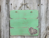 Blank antique green sign with wooden heart hanging on old weathered wood door. Blank green sign with wooden heart hanging on distressed wood fence stock photography
